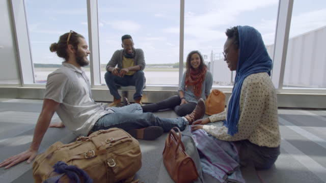 vidéos et rushes de laughing group of diverse young travelers relax in airport terminal near gate. - mode of transport