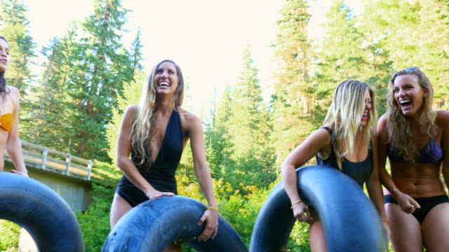 MS PAN Laughing group of female friends standing on log holding inner tubes after floating in river