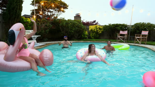 MS Laughing group of friends playing with ball during pool party on summer evening