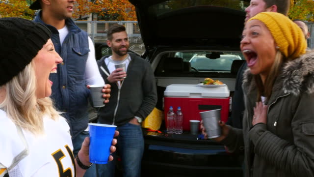 MS Laughing group of friends watching man attempt to kiss friends wife during tailgating party in stadium parking lot