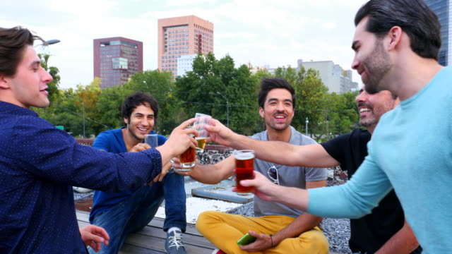 ms swish pan laughing group of male friends toasting glasses together on rooftop deck during party - modern manhood stock videos & royalty-free footage