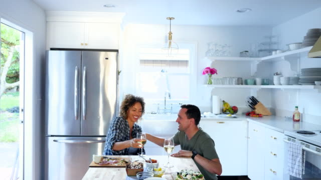 ms zi laughing husband and wife embracing in kitchen - real wife sharing stock-videos und b-roll-filmmaterial