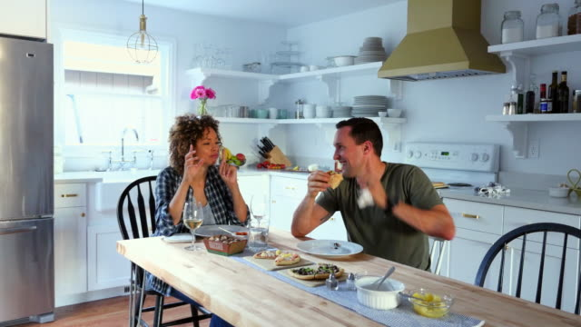 ms laughing husband and wife having dinner in kitchen of home - real wife sharing stock-videos und b-roll-filmmaterial