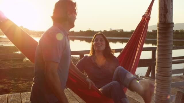 vídeos de stock e filmes b-roll de ms laughing husband swinging wife in hammock on dock at sunset - vedação