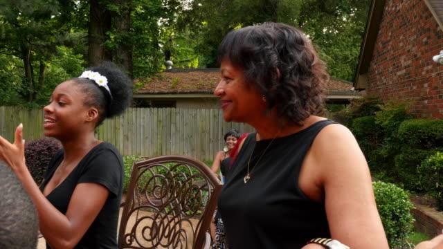 MS PAN Laughing kids playing hand clapping game at table during backyard celebration