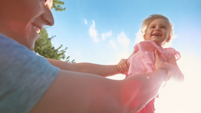 slo mo laughing little girl being raised by her father into in the sky in sunshine - picking up stock videos & royalty-free footage