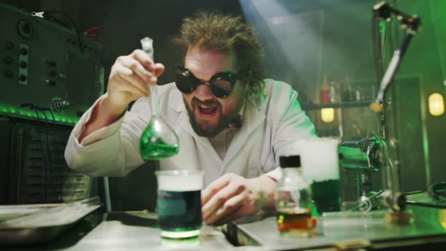 laughing mad scientist mixing liquid in laboratory / cedar hills, utah, united states - wissenschaftliches experiment stock-videos und b-roll-filmmaterial