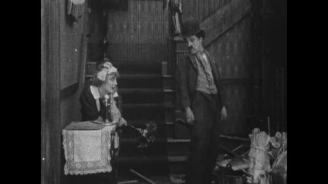 1915 Laughing maid tickles Charlie Chaplin with feather duster
