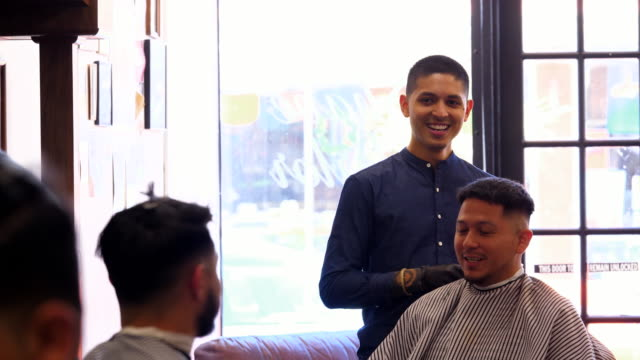 MS Laughing man in discussion with smiling barber while having hair cut in barber shop