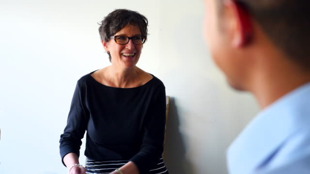 MS Laughing mature businesswoman in discussion with coworkers in office