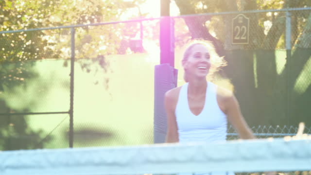 ms laughing mature female playing tennis at net during early morning workout - tennis stock videos & royalty-free footage