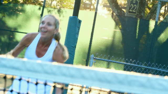 MS Laughing mature female tennis player at net during early morning tennis match