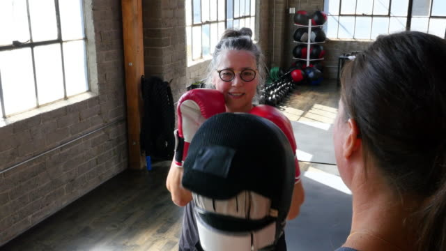 MS Laughing mature woman boxing with coach in gym