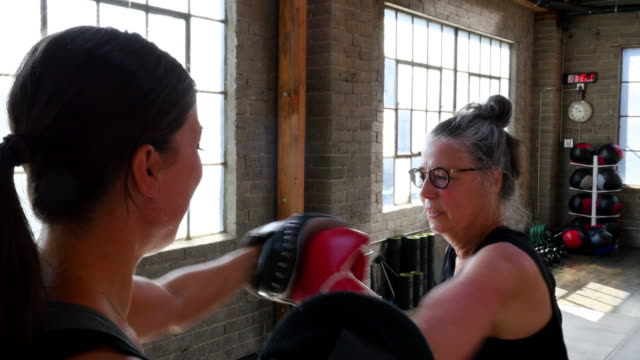 MS ZI ZO Laughing mature woman boxing with coach in gym