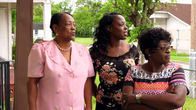 ms laughing mother and adult daughters standing on front porch of home before church - motivo floreale video stock e b–roll