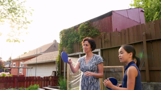 MS Laughing mother and daughter playing ping pong with family on summer evening in backyard of home