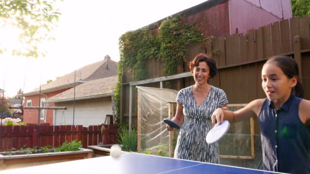 ms laughing mother and daughter playing ping pong with family on summer evening in backyard of home - real people stock videos & royalty-free footage