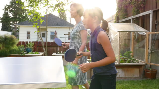 ms laughing mother and daughter playing ping pong with family on summer evening in backyard of home - bordtennis bildbanksvideor och videomaterial från bakom kulisserna