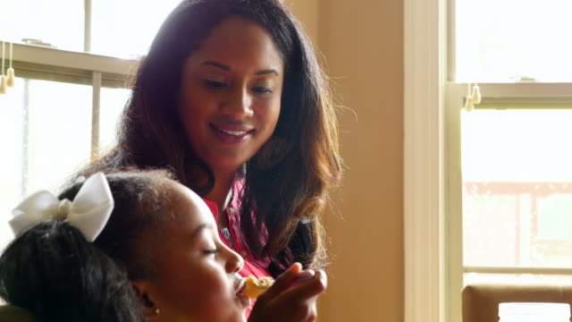 MS Laughing mother eating breakfast with young daughter