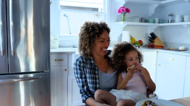 vidéos et rushes de ms laughing mother holding young daughter on lap during dinner with family in kitchen - deux parents