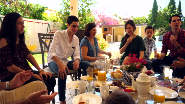 pan ws laughing multigenerational family hanging out during outdoor brunch - elegance stock videos & royalty-free footage