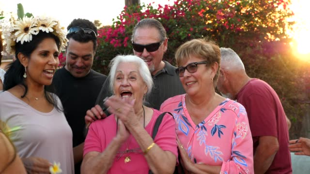 r/f laughing multigenerational family posing for photo during backyard party on summer evening - community stock videos & royalty-free footage