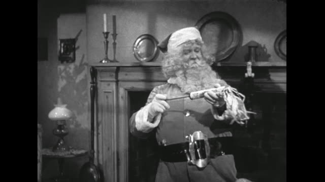 vídeos de stock e filmes b-roll de 1946 laughing santa climbs down chimney and begins happily unpacking and placing toys - meia calça