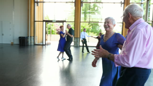 ms laughing senior couple dancing in community center - 70 79 years stock videos and b-roll footage
