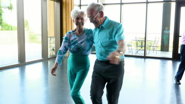 vidéos et rushes de ms laughing senior couple dancing together in community center - retraite