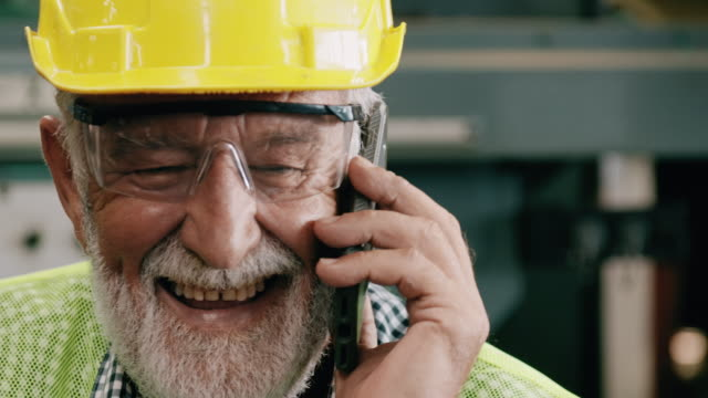 laughing senior industrial worker talking on phone. slowmotion, caucasian male, overalls, helmets. industrial and manufactory concept. - non us location stock videos & royalty-free footage