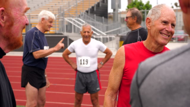 ms laughing senior male track athletes hanging out after running race - weiser mann stock-videos und b-roll-filmmaterial