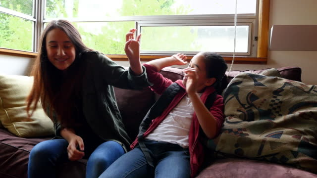 MS Laughing sisters in discussion in living room before school