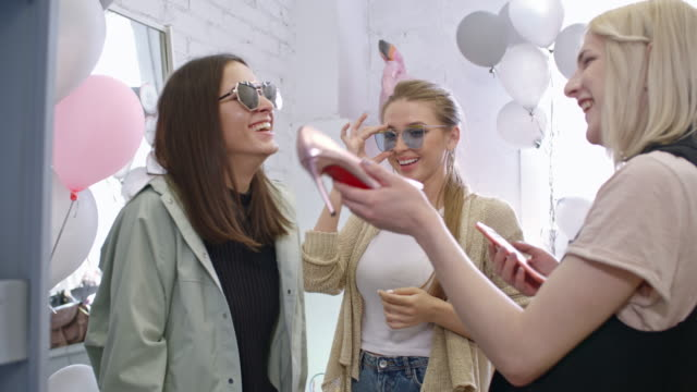 Laughing transgender person and female friends having fun in boutique