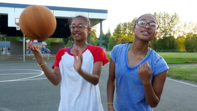 MS Laughing twin sisters on court after playing basketball on summer evening