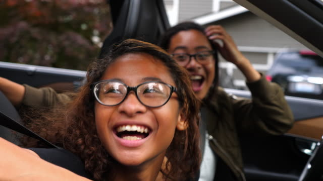 ms laughing twin sisters sitting in front seat of parked car during driving lesson - twin stock videos & royalty-free footage