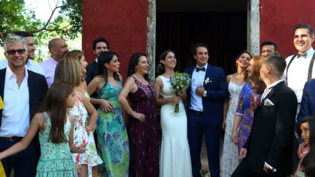 ms laughing wedding party posing for photo while standing outside of chapel at destination wedding - large group of people stock videos & royalty-free footage