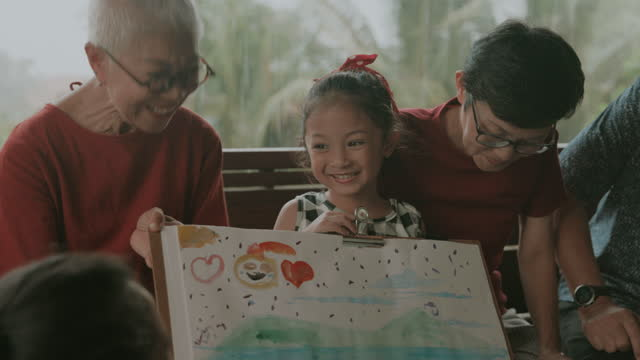 laughing with love, cute girl shows art and craft product to grand parent beside family-stock video - drawing artistic product stock videos & royalty-free footage