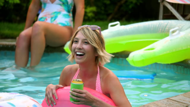 ms laughing woman floating in inner tube during backyard pool party - flamingo bird stock videos & royalty-free footage