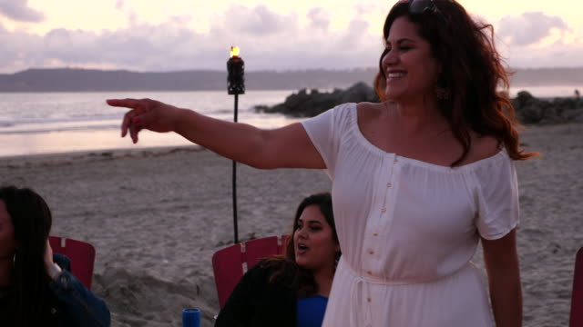 ts laughing woman hanging out with family by fire during beach party - beach holiday stock videos & royalty-free footage