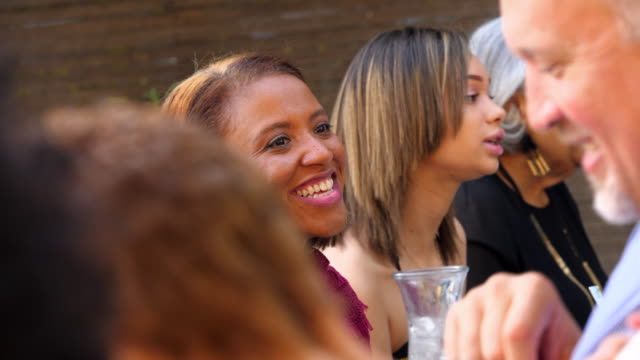 CU Laughing woman in discussion with family members during outdoor family celebration
