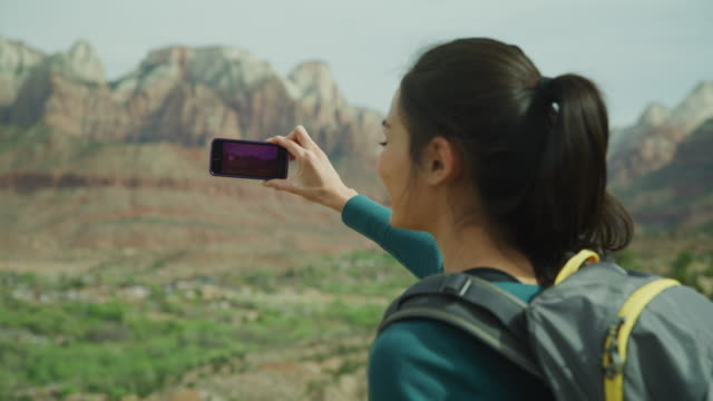 laughing woman photographing scenic view of mountain with cell phone / springdale, utah, united states - photographing stock videos & royalty-free footage