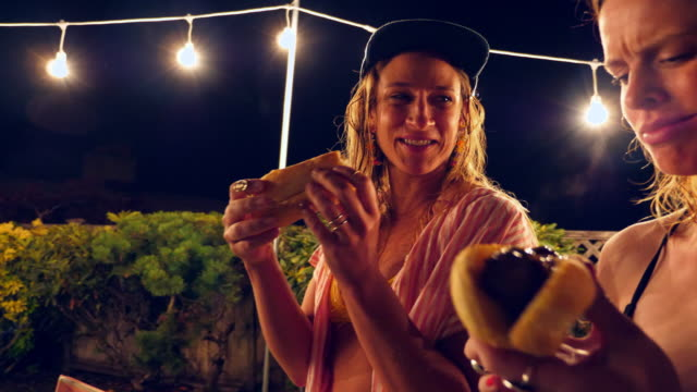 ms laughing women eating hot dogs after backyard pool party on summer evening - hot dog stock videos & royalty-free footage
