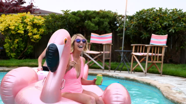 MS Laughing women floating on pool toy during party on summer evening