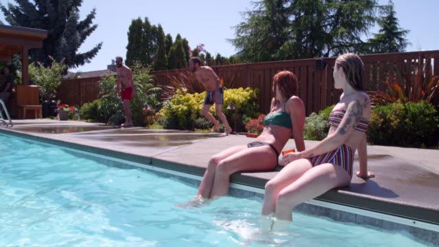 ms  slo mo laughing women sitting pool side watching friends running and jumping into pool - badbyxor bildbanksvideor och videomaterial från bakom kulisserna