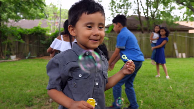ms laughing young boy blowing bubbles during backyard party - innocenza video stock e b–roll