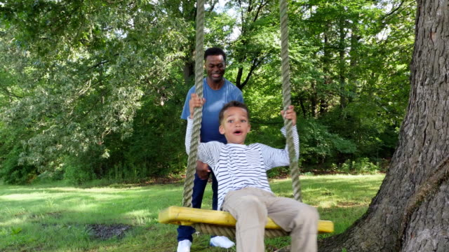 ms laughing young boy leaning back looking at father while swinging on backyard swing - pushing stock videos and b-roll footage