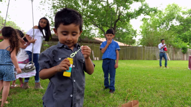 MS Laughing young boy playing with bubbles during backyard party