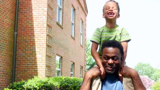 MS Laughing young boy riding on fathers shoulders walking through park on summer afternoon