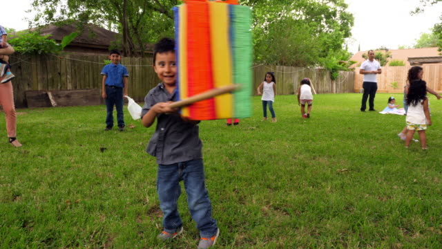 vídeos de stock e filmes b-roll de ms laughing young boy trying to break open pinata during family birthday party - 4 5 anos