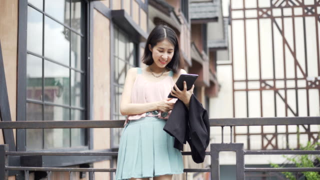 Laughing young Chinese businesswoman using tablet pc computer or smart phone outside office building